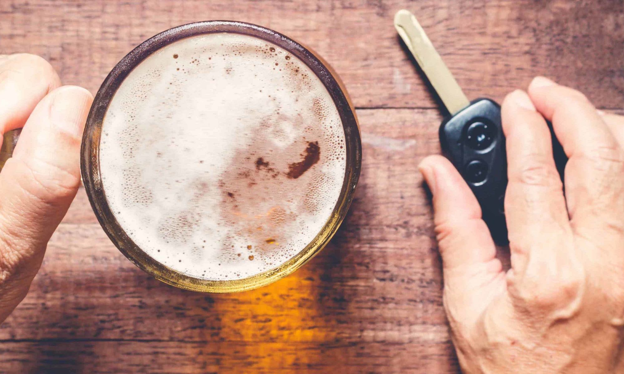 A man's hands holding a car key next to a beer, representing DUI's