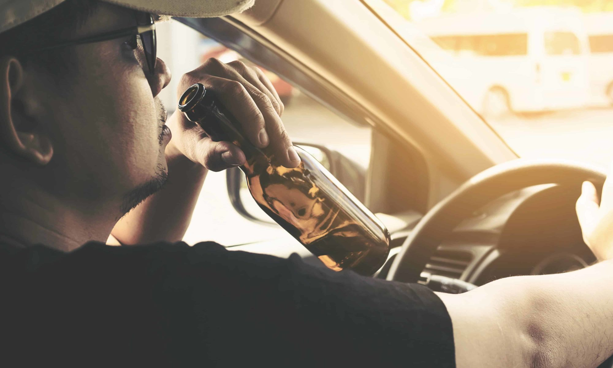 A man drinking a beer while driving, violating Arizona open container laws
