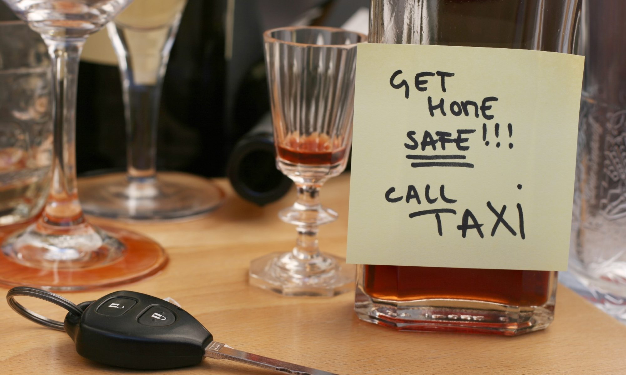 "An alcoholic drink next to car keys, labeled ""Get home safe! Call taxi"" to avoid a DUI"