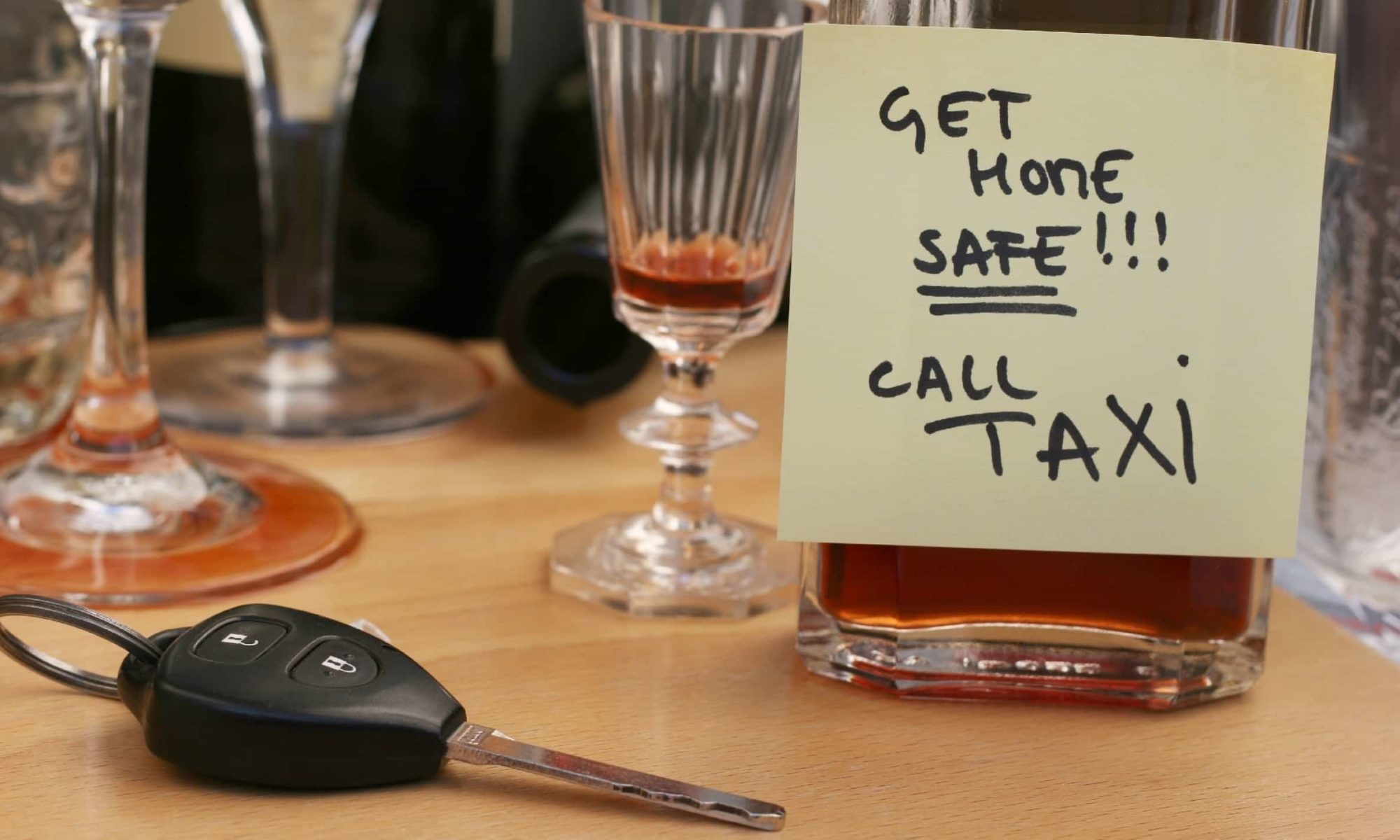 """An alcoholic drink next to car keys, labeled """"Get home safe! Call taxi"""" to avoid a DUI"""