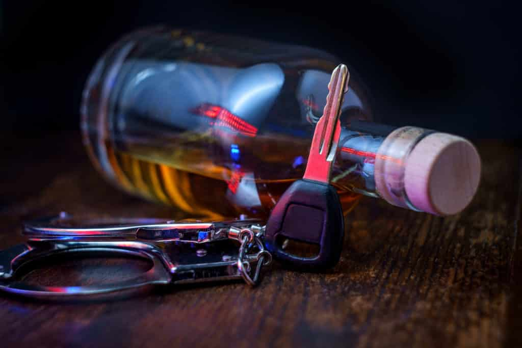 Keys by a bottle of alcohol, depicting a DUI offense
