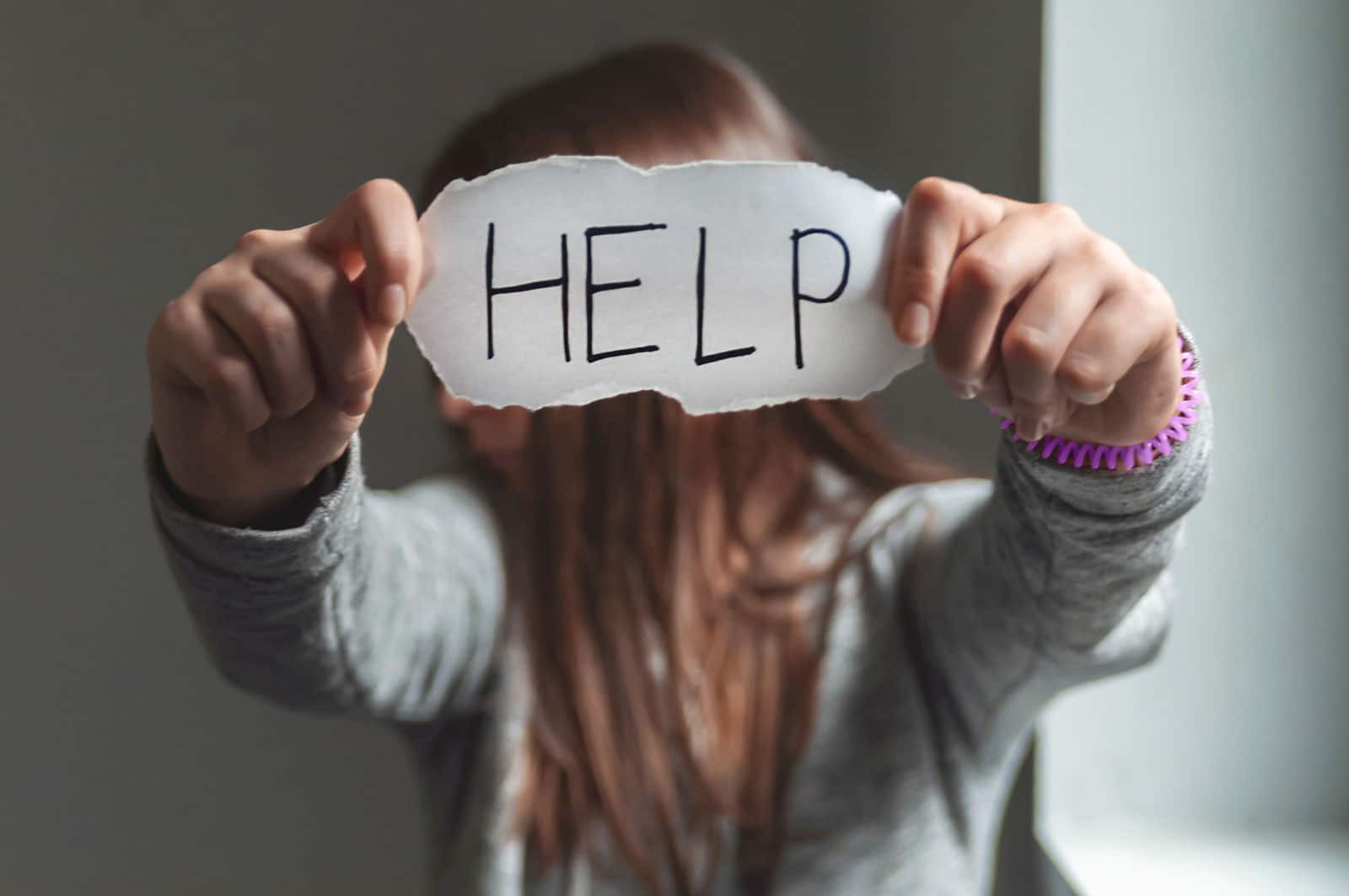A woman holding up a piece of paper that says 'Help,' representing domestic violence