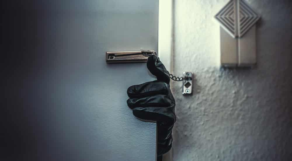 A gloved hand entering a home during the course of a property crime