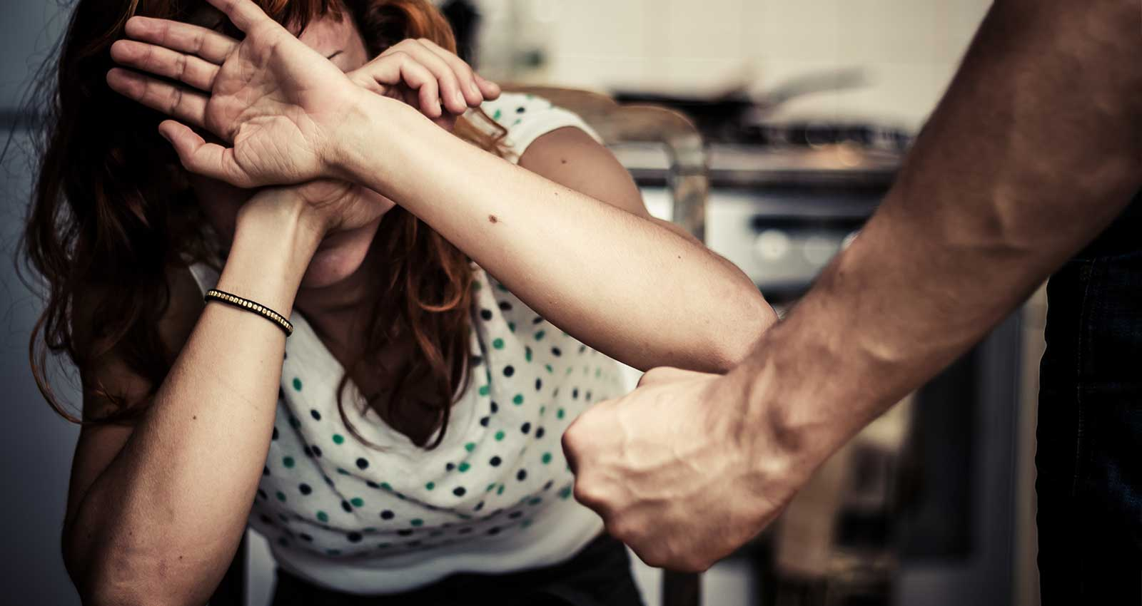 A woman cowering as a man raises his fist in a domestic violence situation