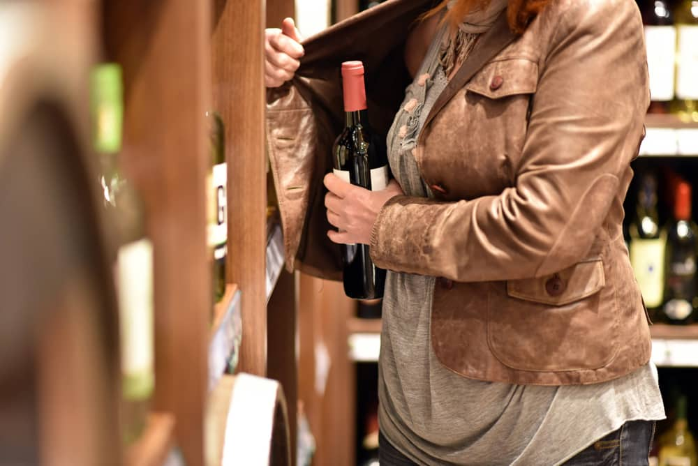 A woman shoplifting a bottle of wine
