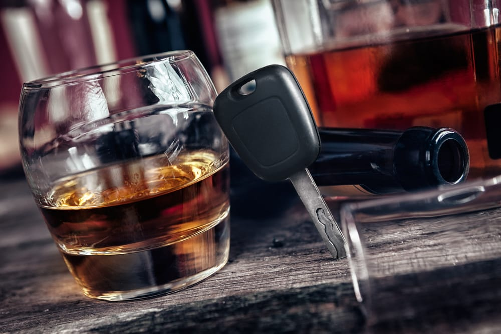A set of car keys leaning against a glass of alcohol. Driving under the influence can lead to an aggravated DUI