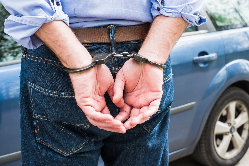 A man with his hands cuffed behind his back during an arrest for felony