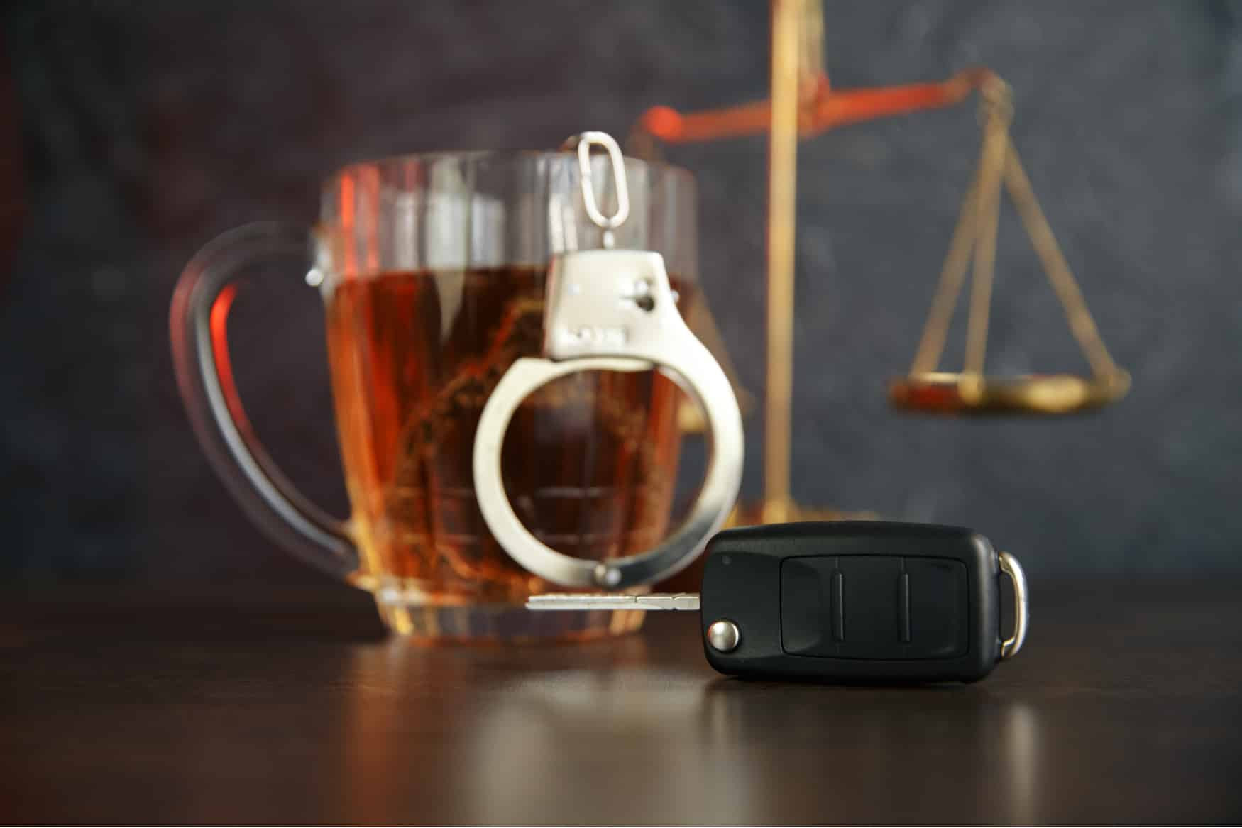 A scale, handcuffs, a drink, and car keys on a desk to represent a DUI attorney