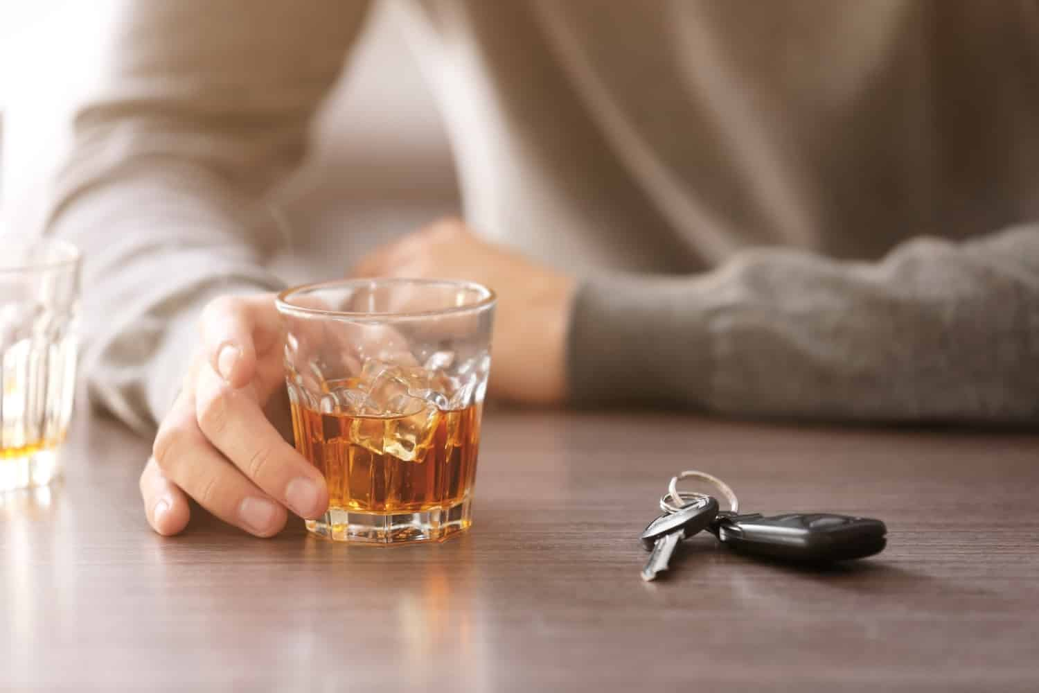 A person drinking with a pair of keys in front of them. If they drink and drive, they may face harsh Arizona DUI penalties