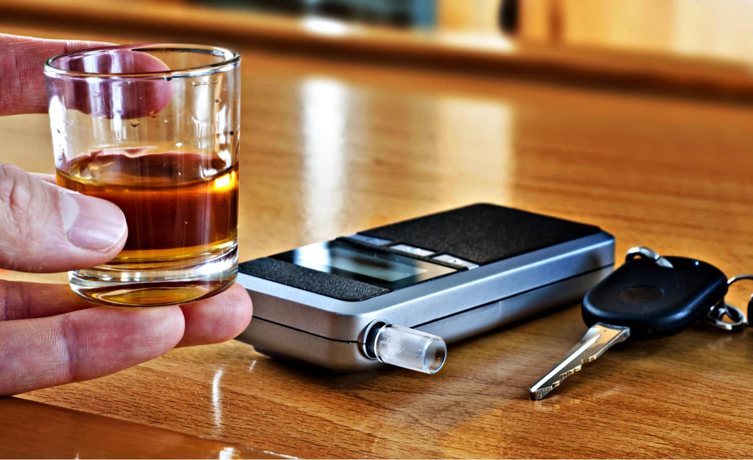 A breathalyzer next to keys on a wooden table and someone who may be over the legal alcohol limit holding a shot glass