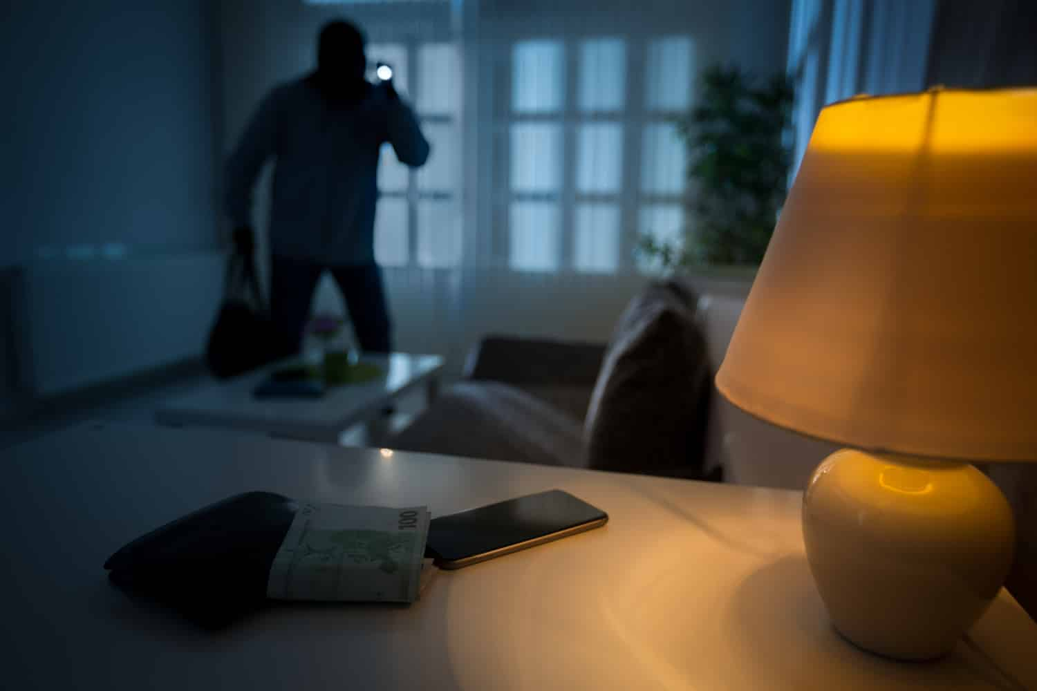 A man in a dark home committing burglary