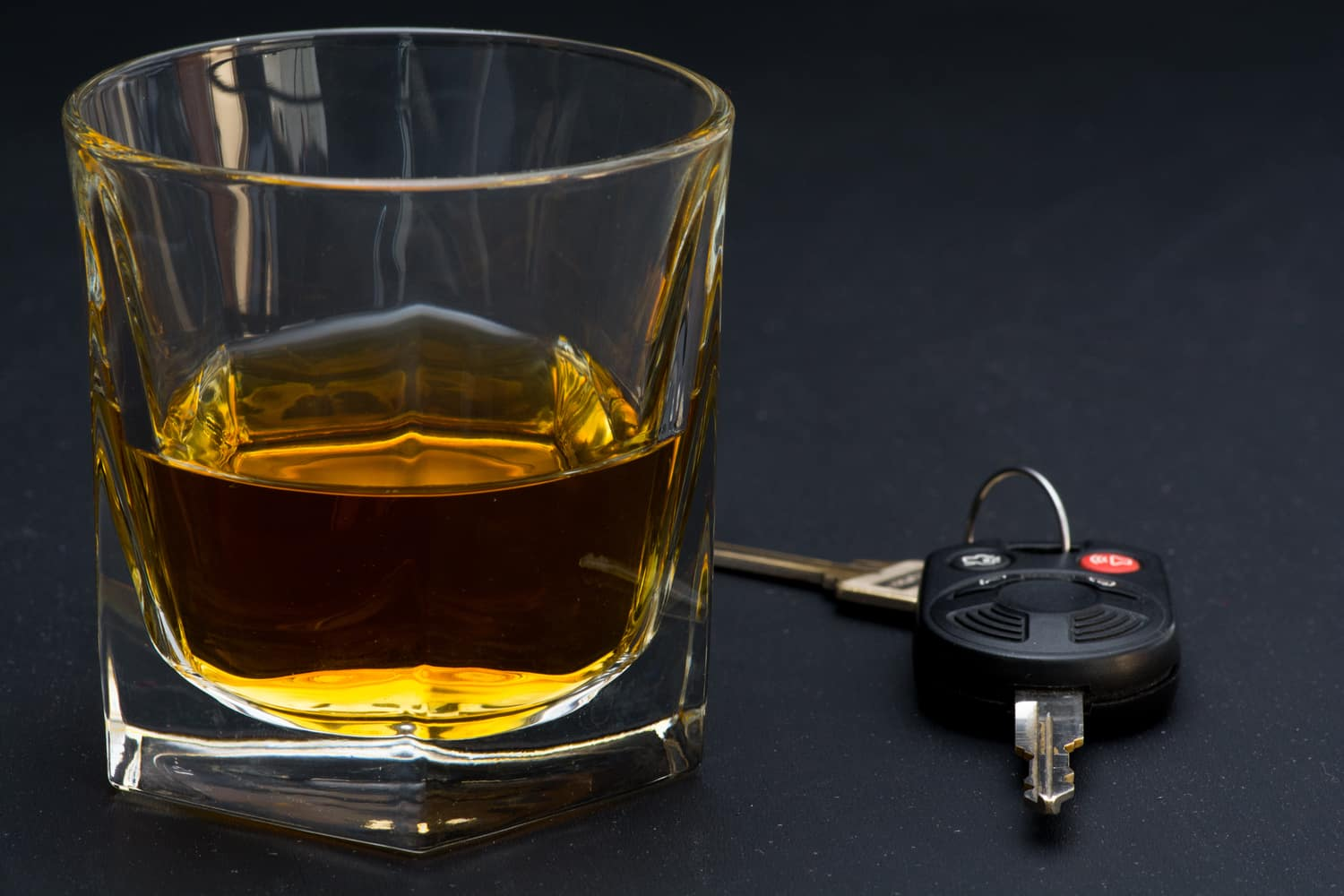Car keys next to a glass of alcohol to represent DWI