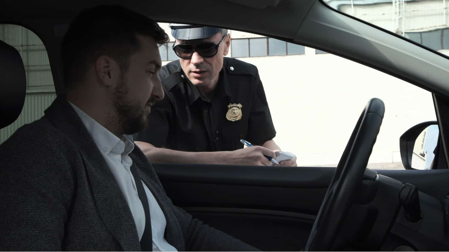 A man in a business suit talking to a police office. When can police search your car? Read our blog to find out