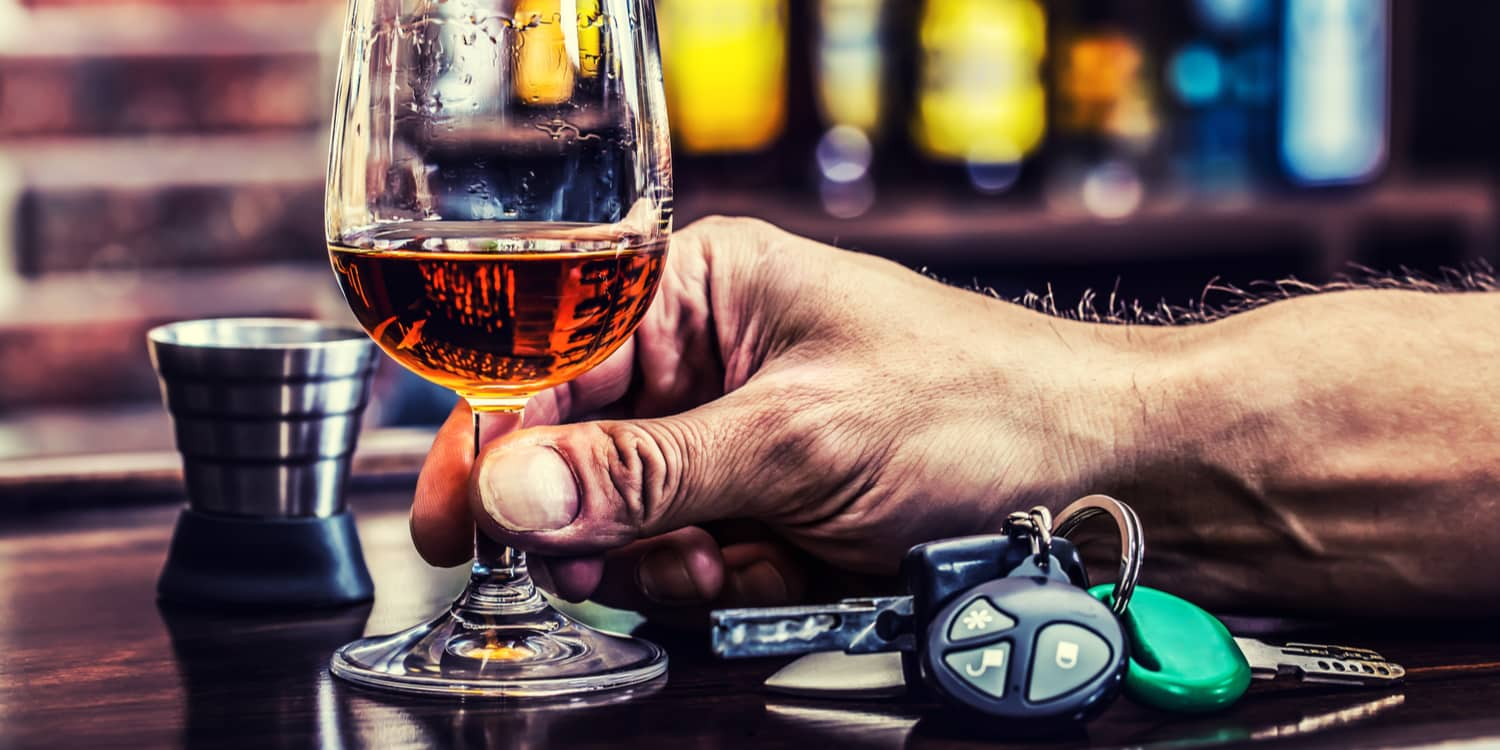 A person holding a drink with car keys next to them, representing questions about DUI