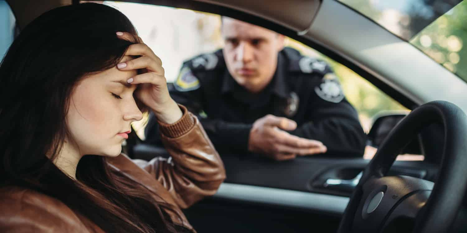 A woman being pulled over after driving with a suspended license