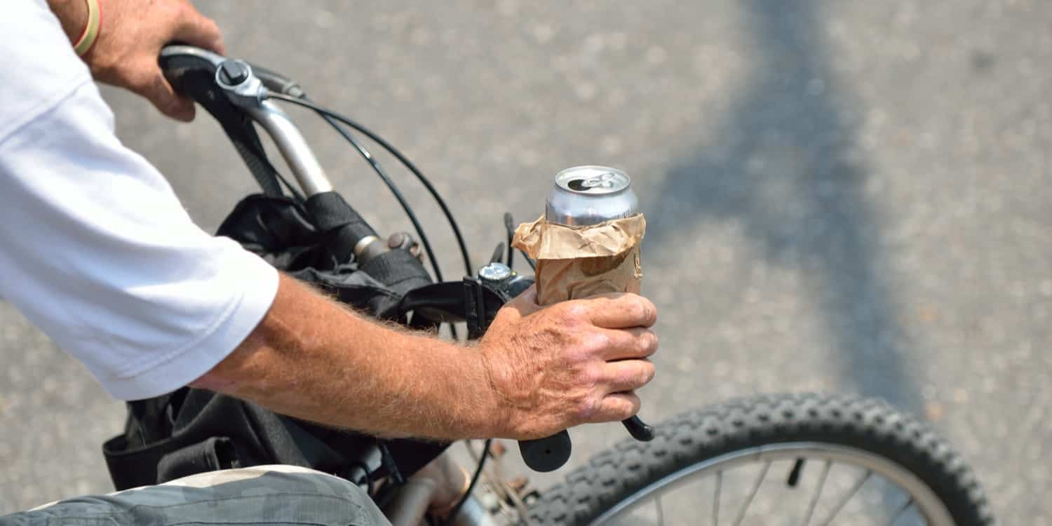 A man drinking and biking (note: there is no DUI on a bike in Arizona)