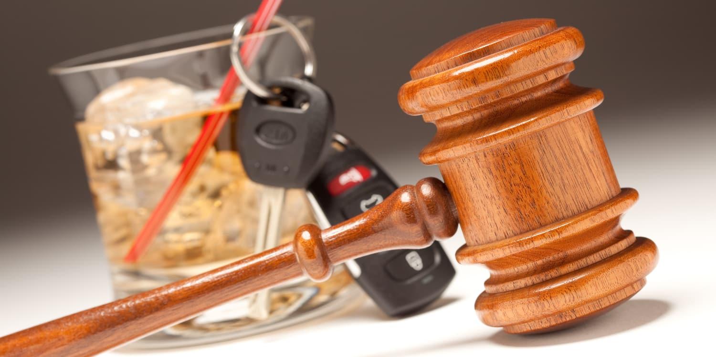 A gavel next to car keys and alcohol, representing DUI defenses
